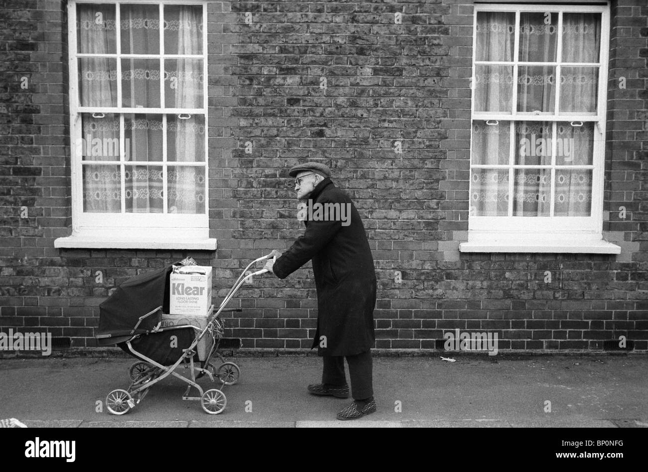 La vecchiaia pensionato spingendo lo shopping home in una carrozzina. Battersea London 1970S UK HOMER SYKES Immagini Stock
