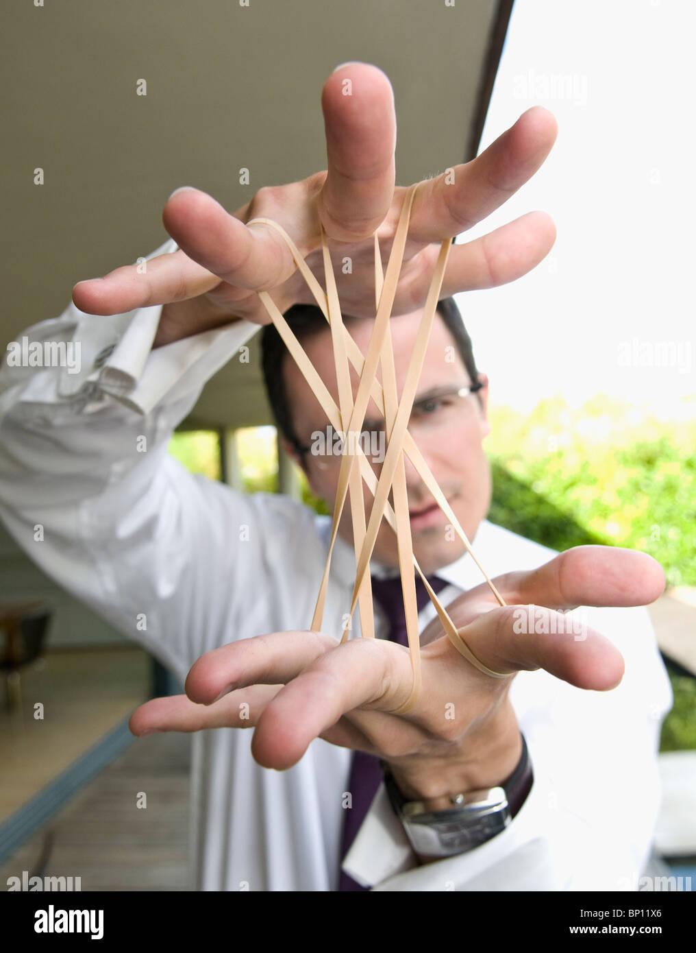 L uomo si estende fasce elastiche Immagini Stock