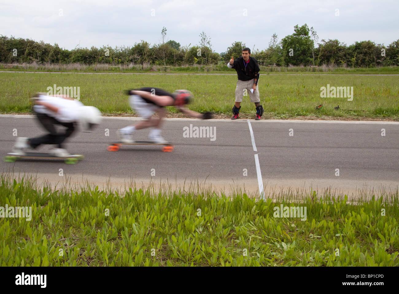 Due downhill longboard skateboard gravità racers avvicinarsi alla linea di finitura Immagini Stock