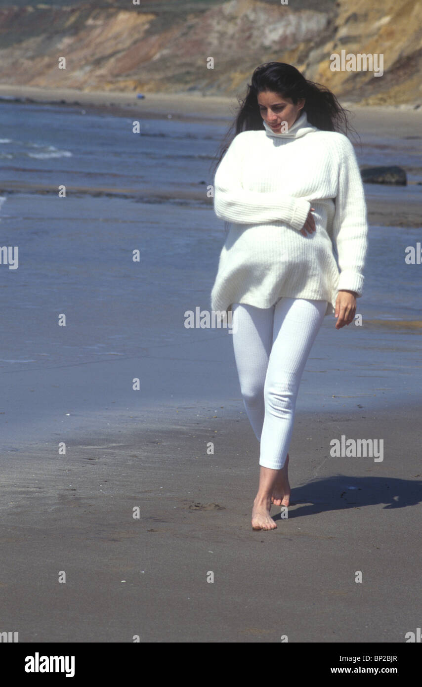 39b59d86f778 Razza mista pesantemente la donna incinta di camminare sulla spiaggia  caldamente vestito in un ponticello bianco