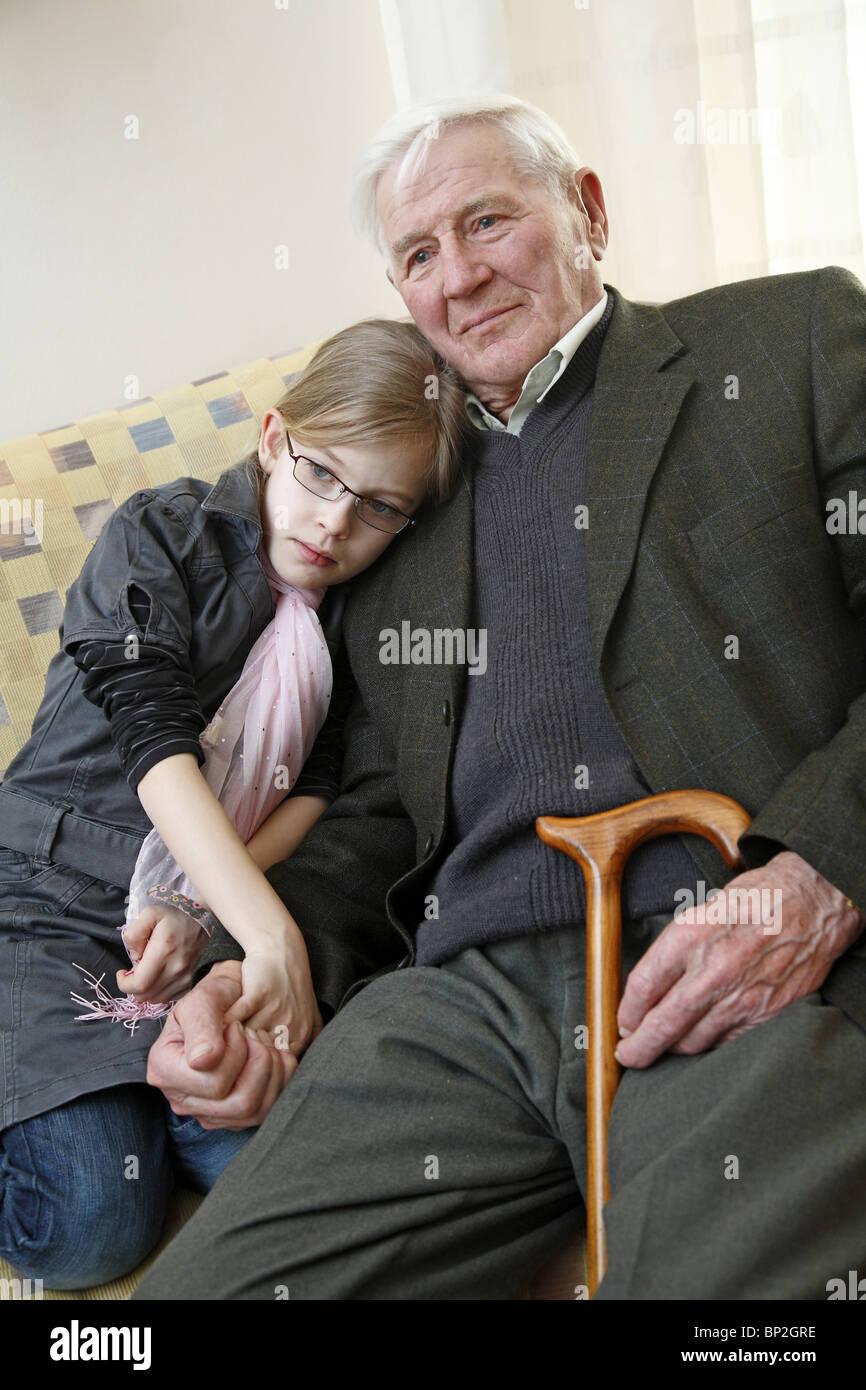 La nipote cuddling fino a suo nonno Immagini Stock