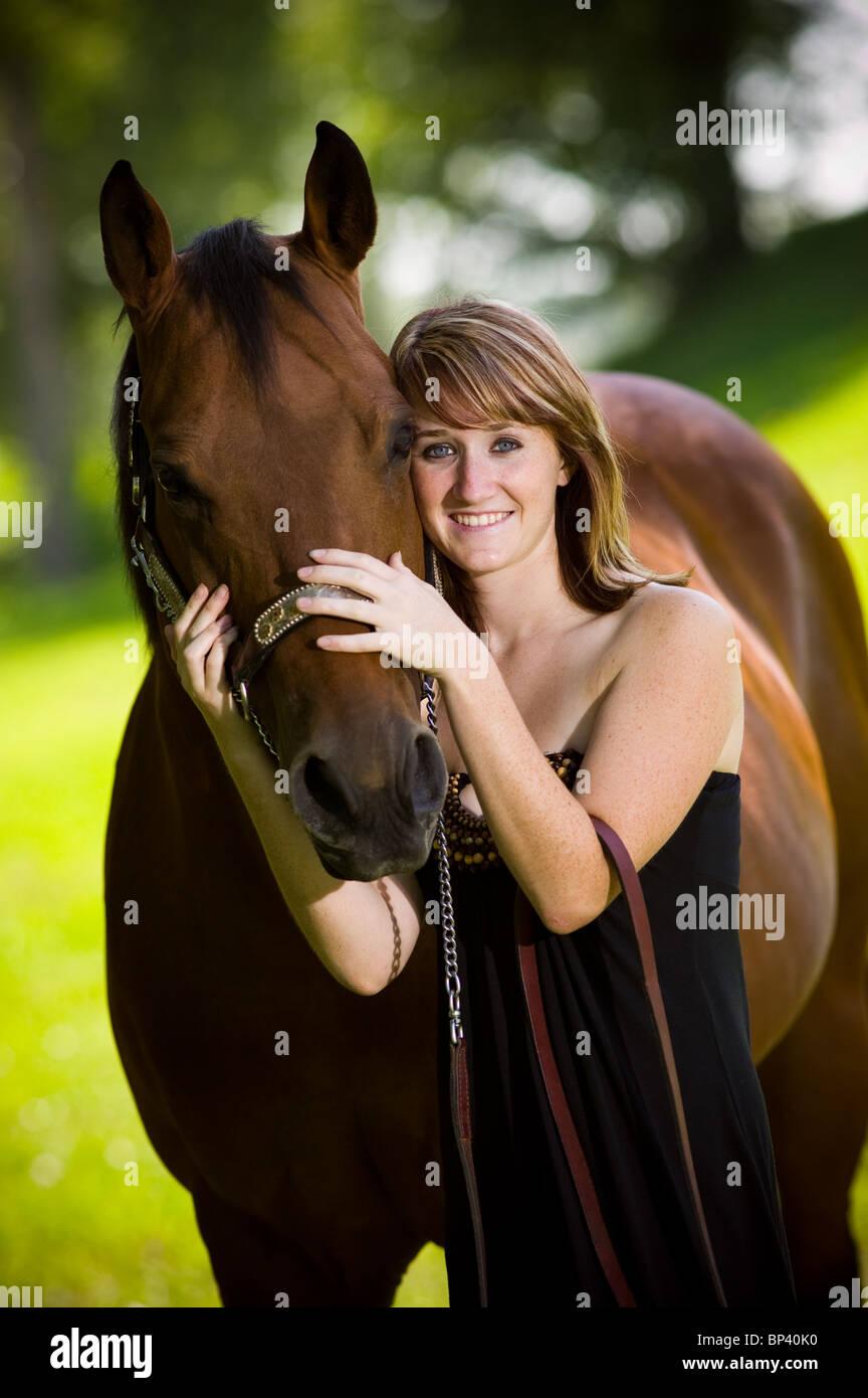 Ritratto di ragazza adolescente 17-18 anni in piedi in posizione di parcheggio con il suo cavallo. Foto Stock