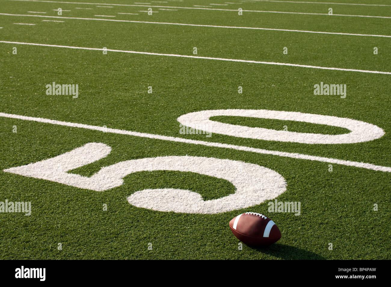 Il football americano sul campo accanto a 50 yard line. Immagini Stock
