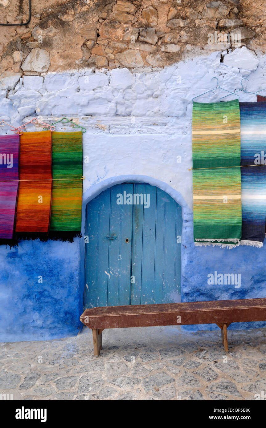 Visualizzazione dei tappeti per la vendita, Blue Door & panca in legno, Chefchaouen, Marocco Immagini Stock
