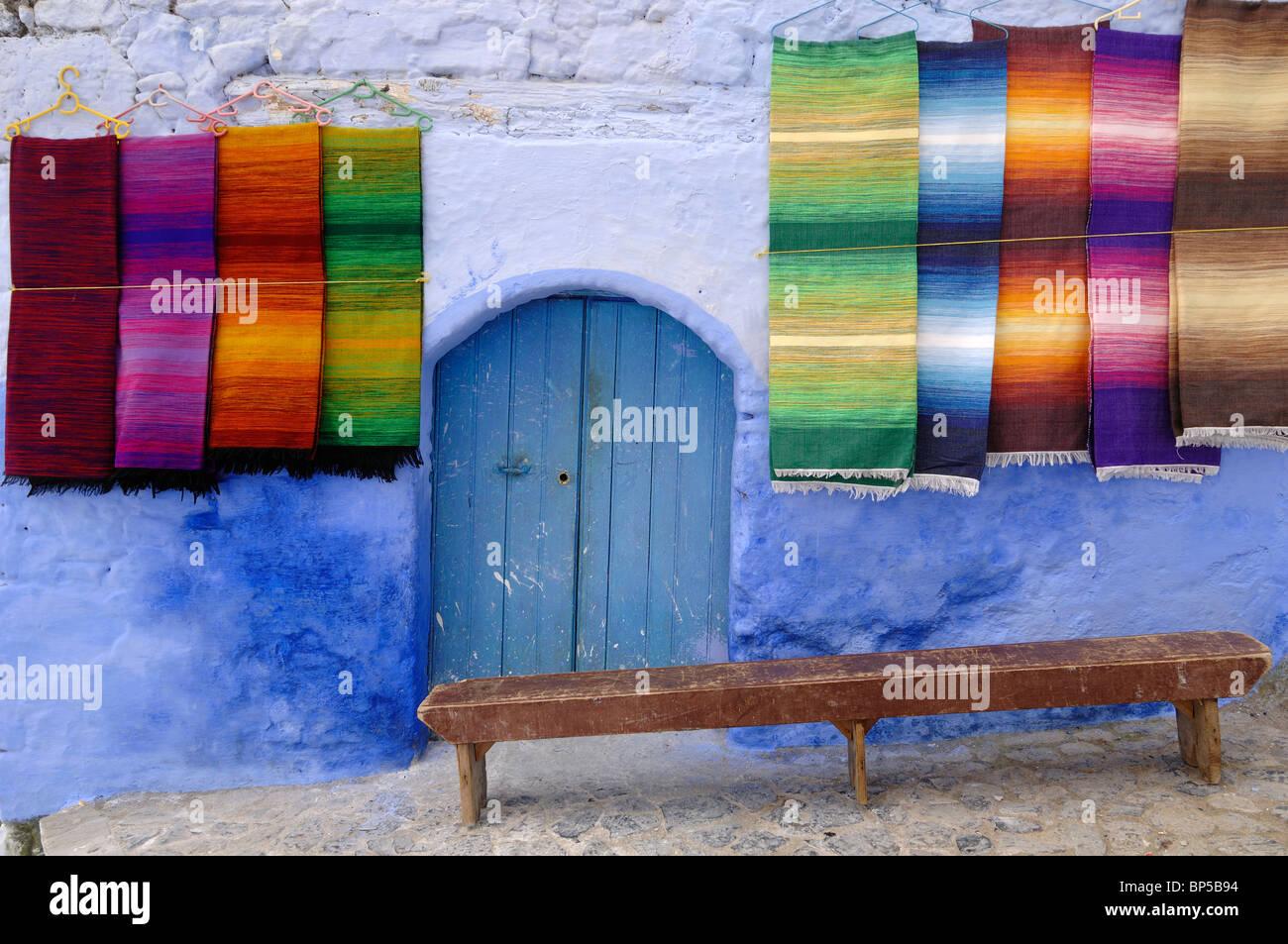 La visualizzazione di tessuti colorati tappeti tappeti sospesi o tappeti per la vendita, blu porta e panca in legno, Immagini Stock