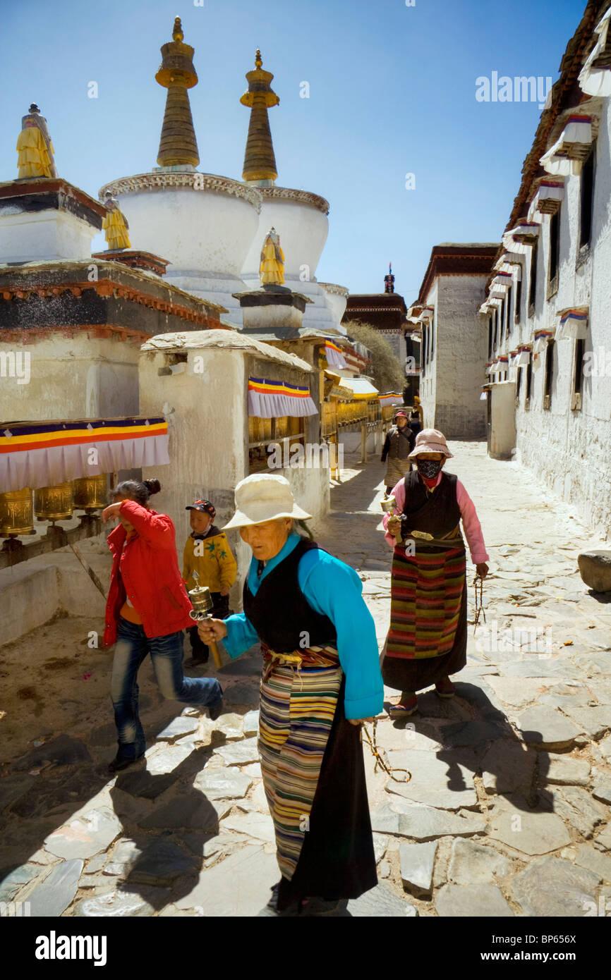 Una famiglia pellegrina a piedi intorno al set di stupa nei cortili del monastero di Tashilhunpo a Shigatse, nel Immagini Stock