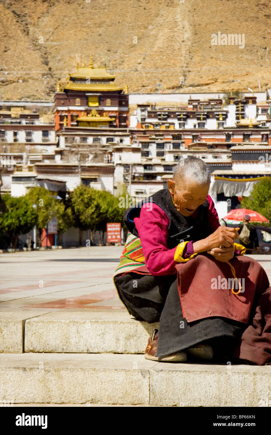 Un pellegrino prende un po' di riposo davanti al monastero di Tashilhunpo a Shigatse, nel Tibet, Cina. 2010 Immagini Stock