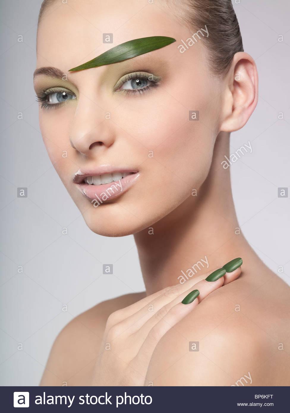 Una donna che indossa il verde smalto per unghie e foglia verde sopracciglio Immagini Stock