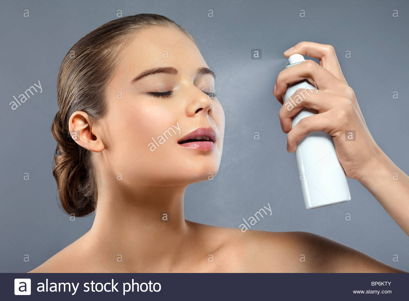 Una donna spruzzando il suo volto con spray idratante Immagini Stock