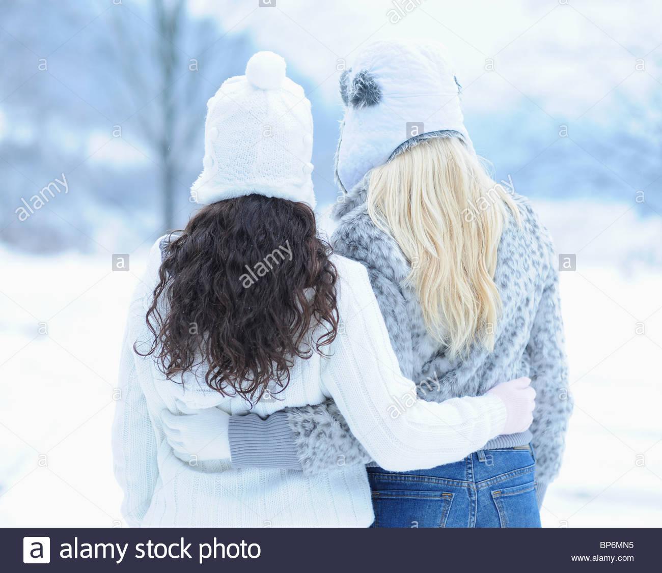 Vista posteriore di due giovani donne costeggiata sulla giornata invernale Immagini Stock