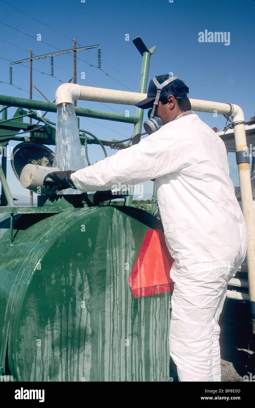 Lavoratore agricolo indossando indumenti protettivi, Immagini Stock