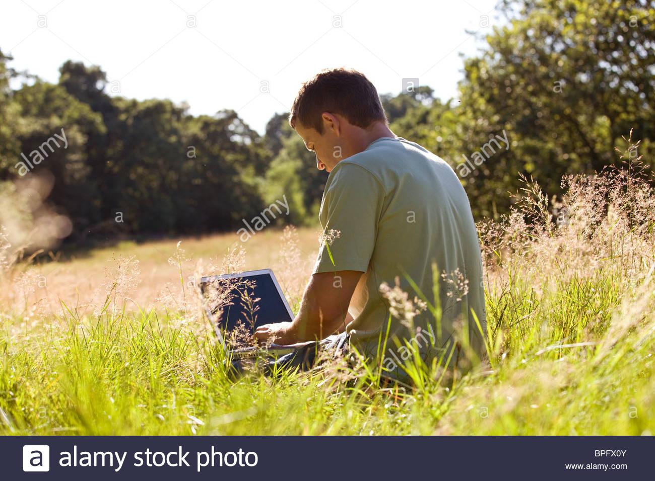 Un giovane uomo seduto sull'erba, usando un computer portatile Immagini Stock