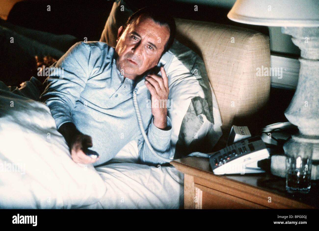 Uomo nel letto sul telefono armi di distrazione di massa; (1997) Foto Stock