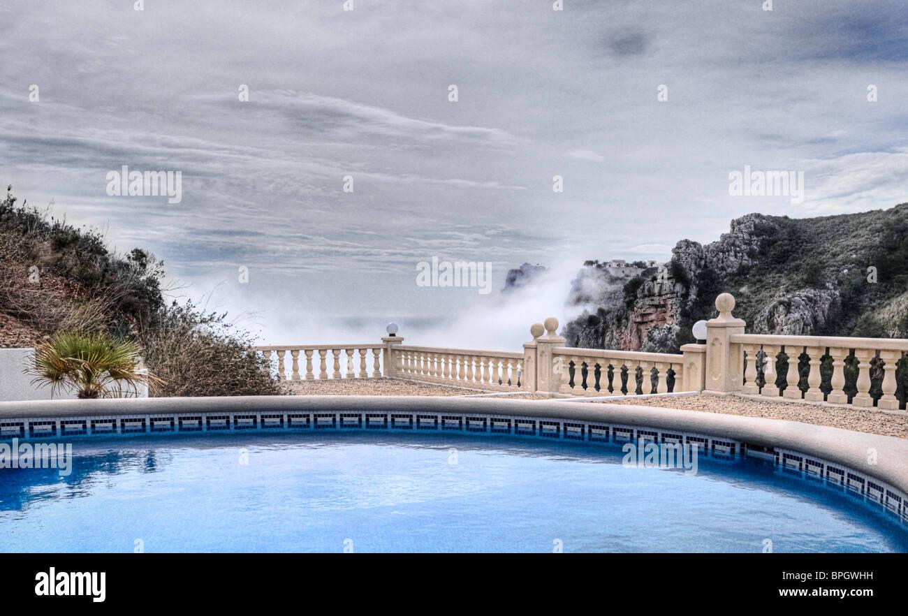 Inquadratura di un Mediterraneo di lusso Piscina, con nebbia che sorgono dal mare Immagini Stock