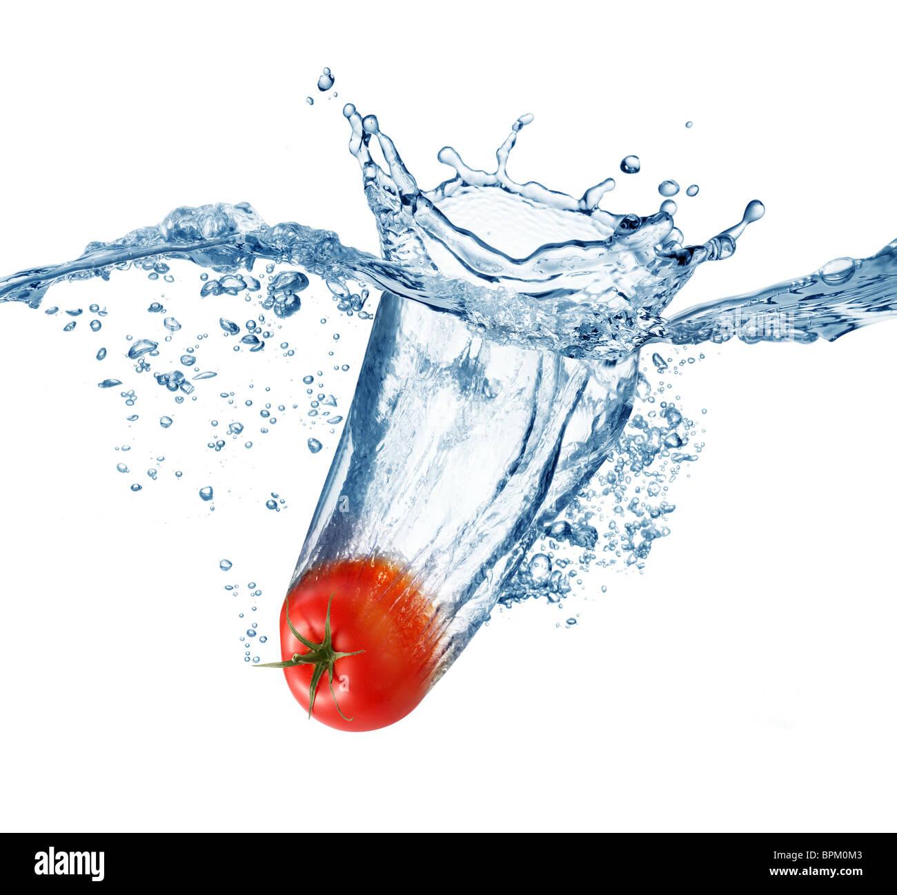 Pomodoro maturo cade profondamente sotto l'acqua con un grande splash. Immagini Stock