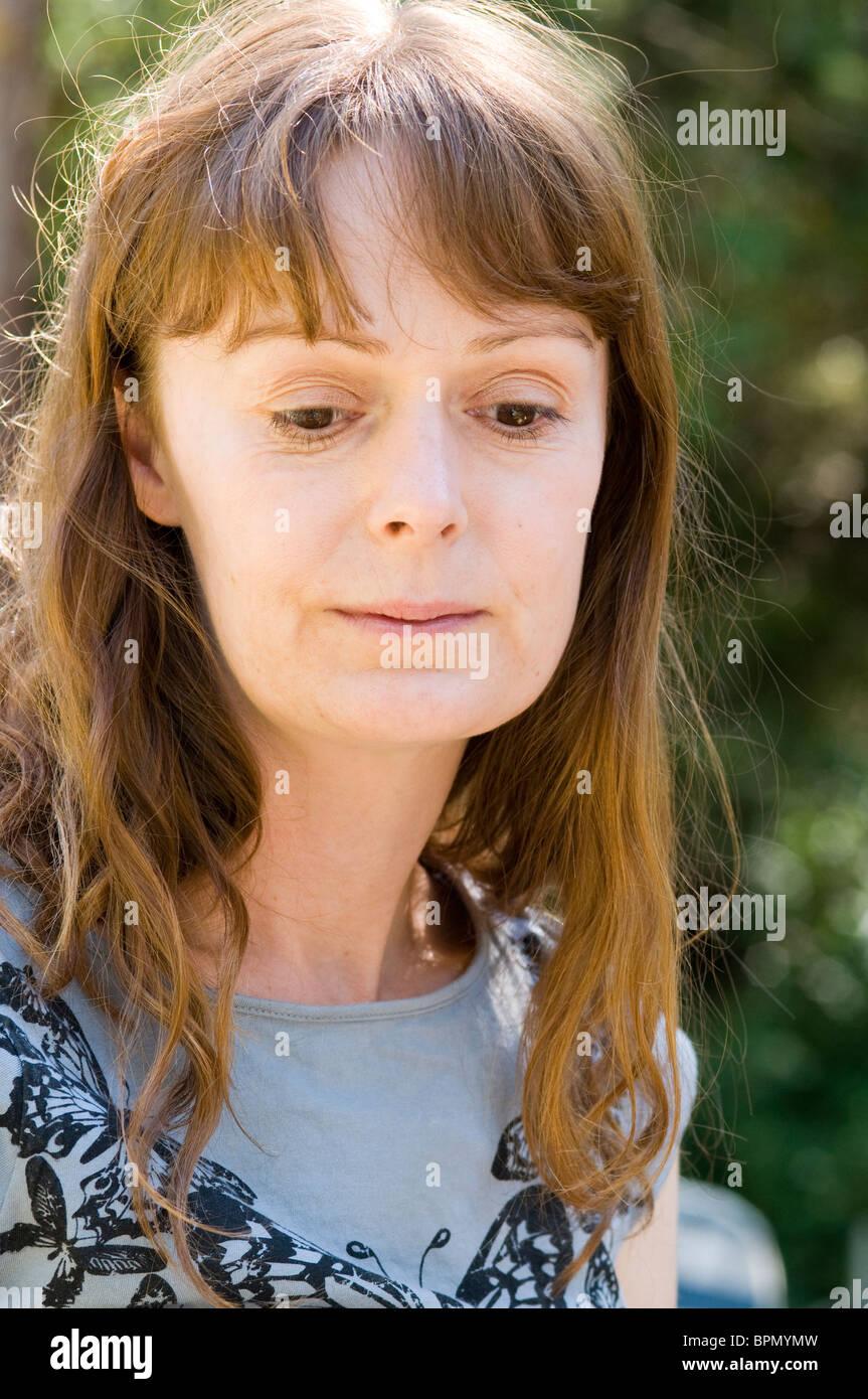 Donna che guarda abbattuto con capelli lunghi marrone Immagini Stock