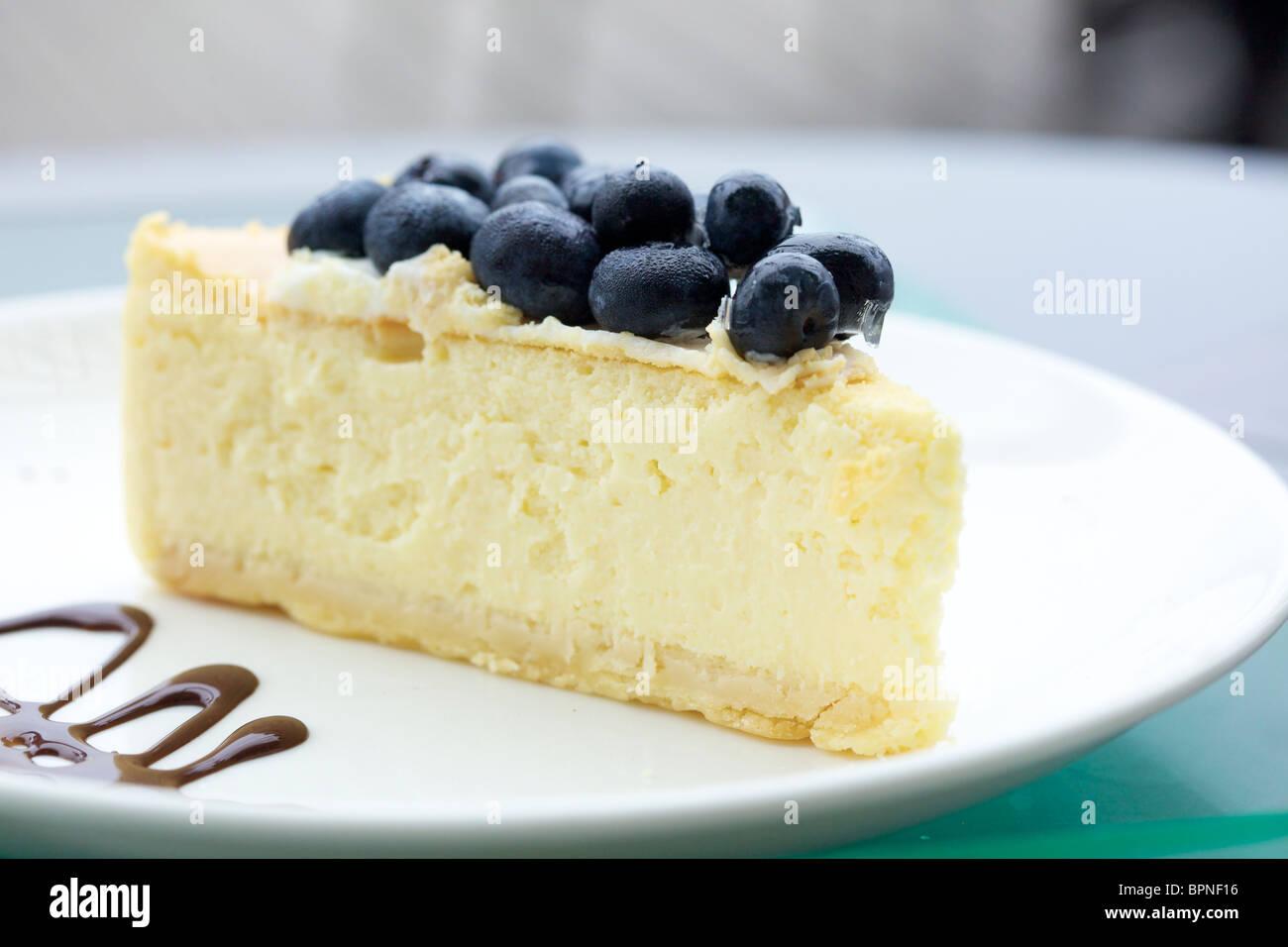 Una fetta di cheesecake al forno con mirtilli freschi sulla parte superiore Foto Stock