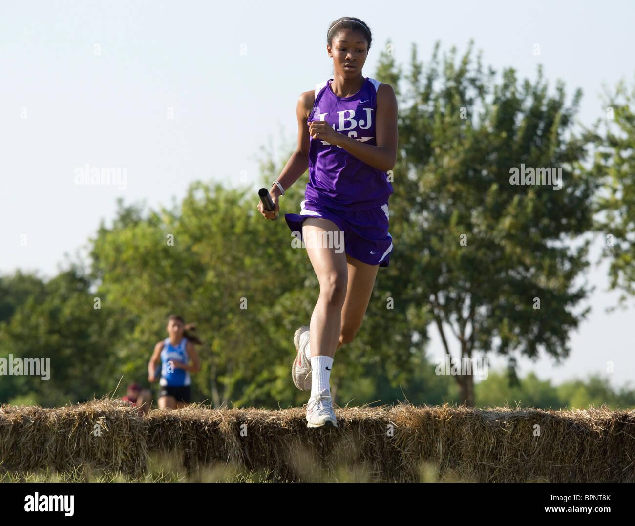 Femmina afro-americano di alta scuola runner salta balla di fieno su cross-country durante incontrate in Pflugerville, Immagini Stock