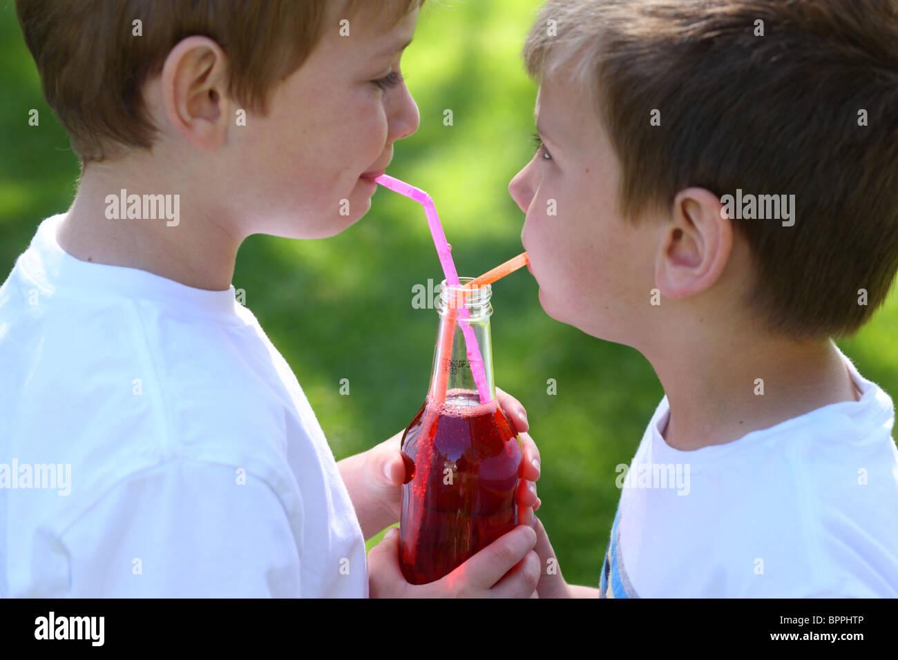 Due giovani ragazzi condividendo una bottiglia di soda Immagini Stock