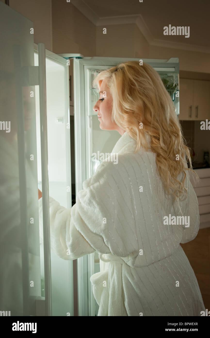 Giovane donna cercando in frigo per uno spuntino di mezzanotte Immagini Stock