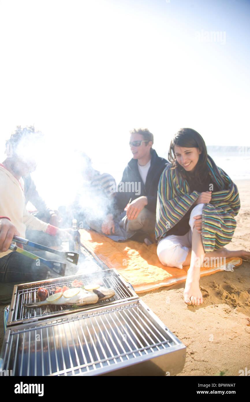 Gruppo di amici seduti intorno a un falò sulla spiaggia Foto Stock