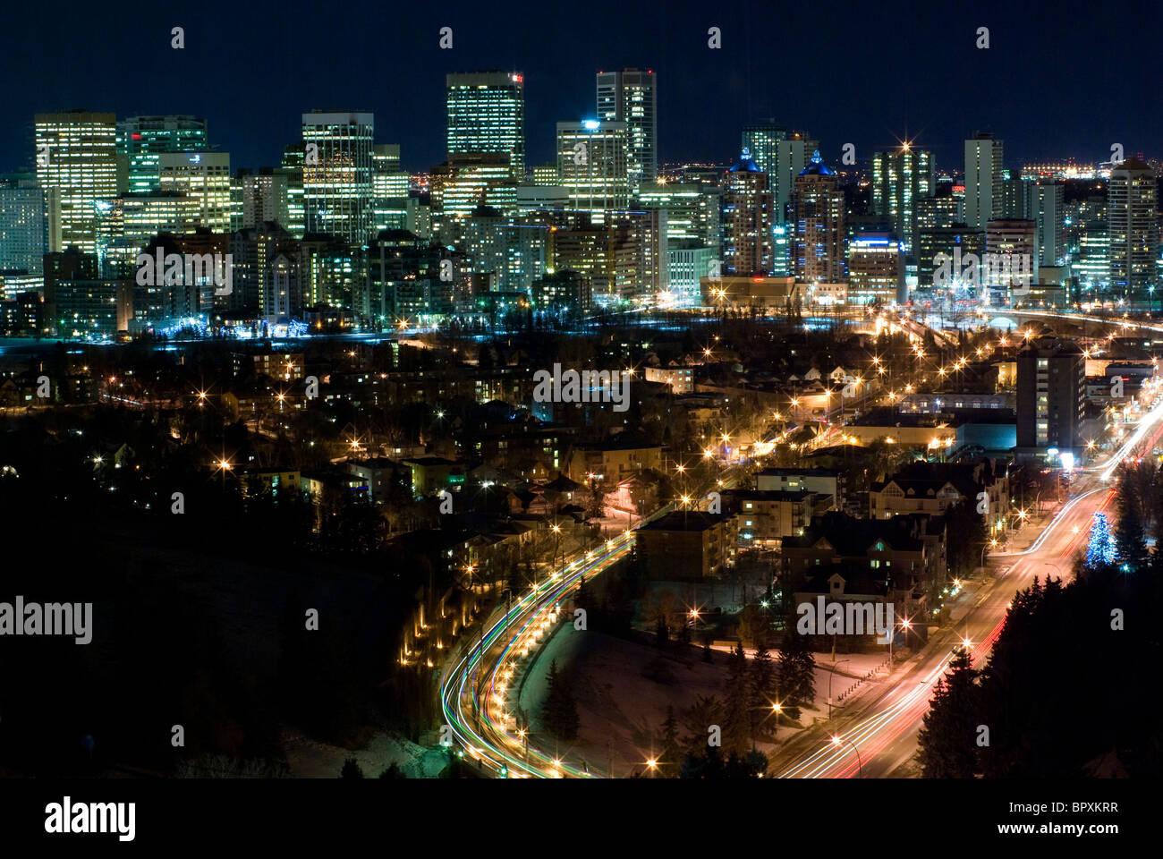 Calgary, Alberta, Canada skyline notturno con un loop di strada con la testa e le luci di coda in primo piano. Immagini Stock