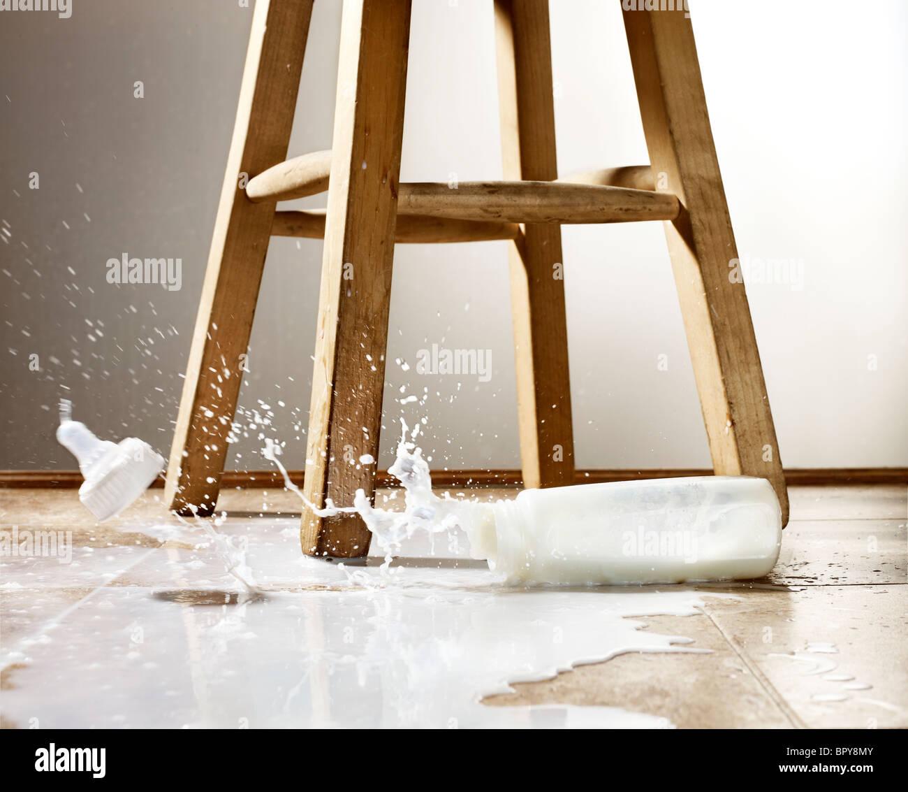 Biberon e latte versato con schizzi sul pavimento Immagini Stock