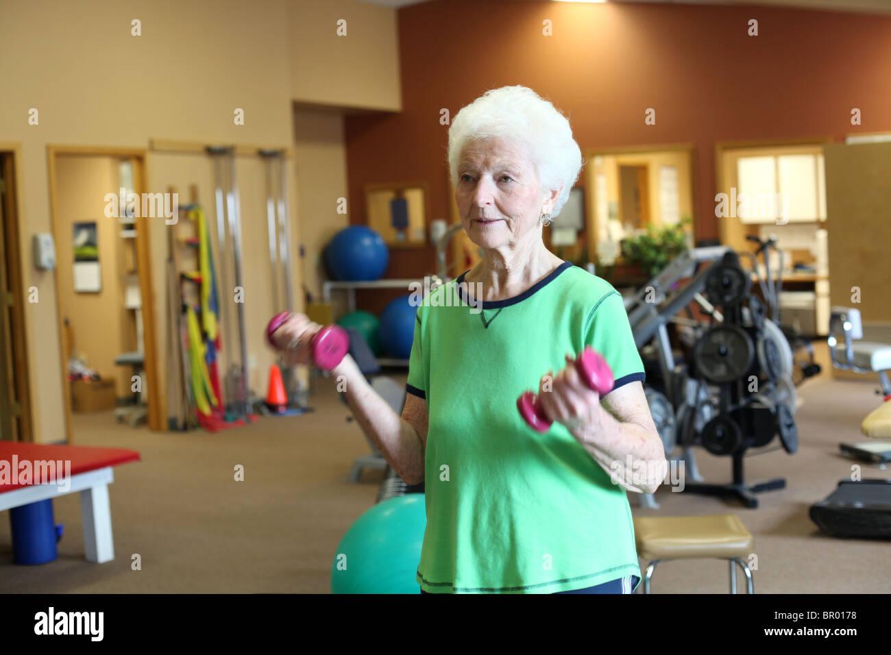 Sana donna senior di esercizio con pesi in palestra Foto Stock