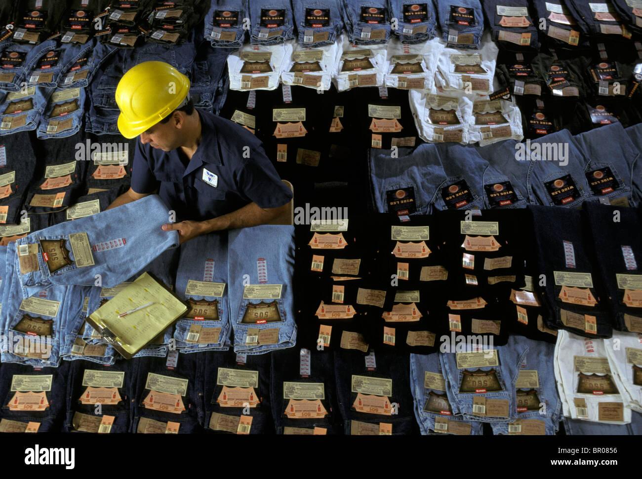 Un collare blu lavoratore guarda al jeans in un negozio di grandi dimensioni. Immagini Stock