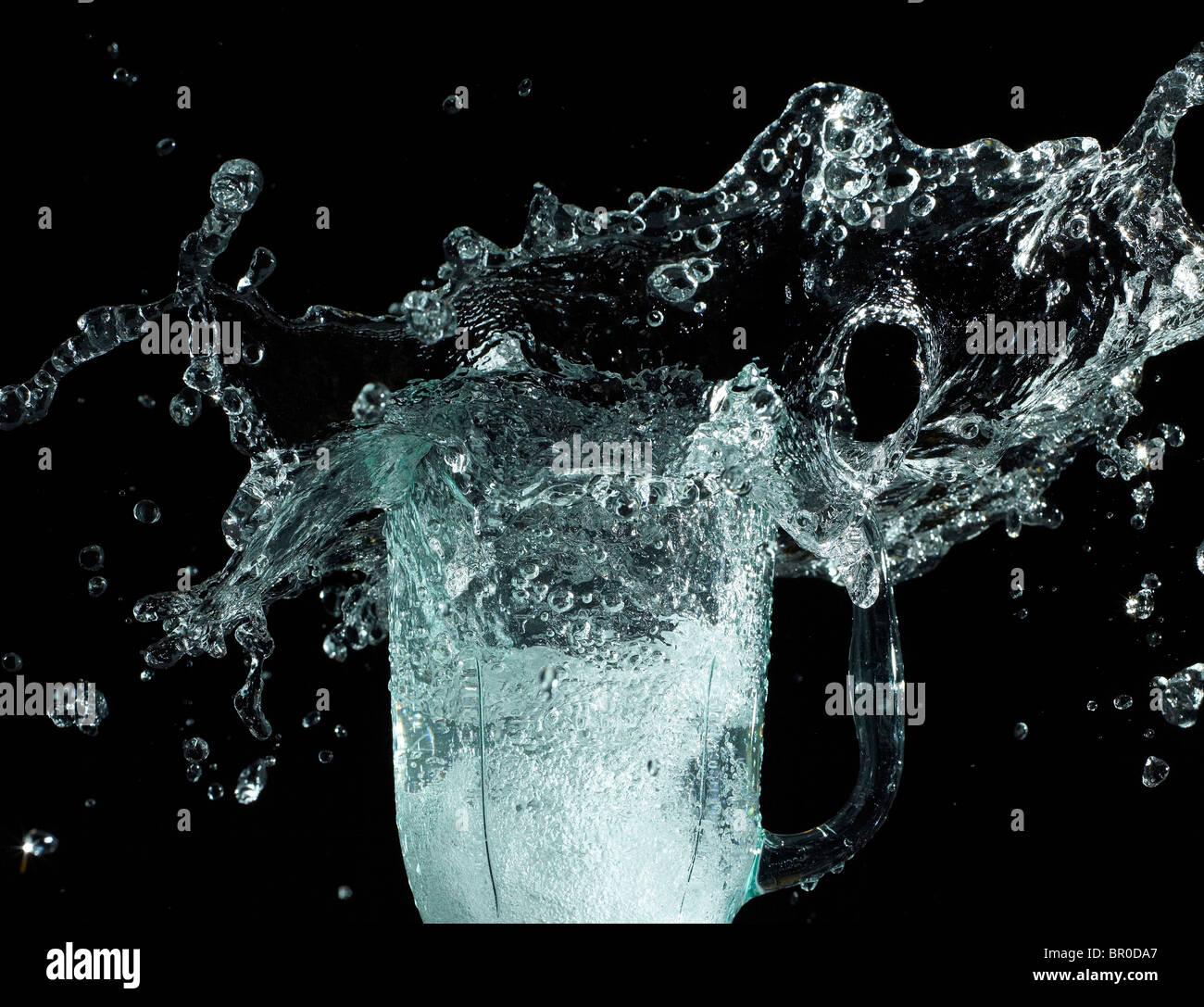 Dinamico con acqua splash su sfondo nero Immagini Stock