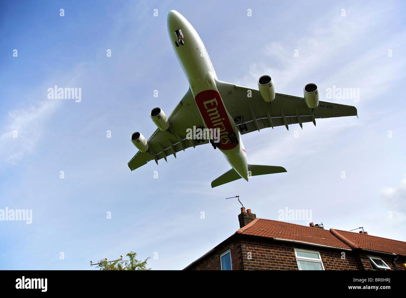 Emirates Airline Airbus A380 arriva all'aeroporto di Manchester, volando a bassa quota sopra la casa sul tetto. Immagini Stock