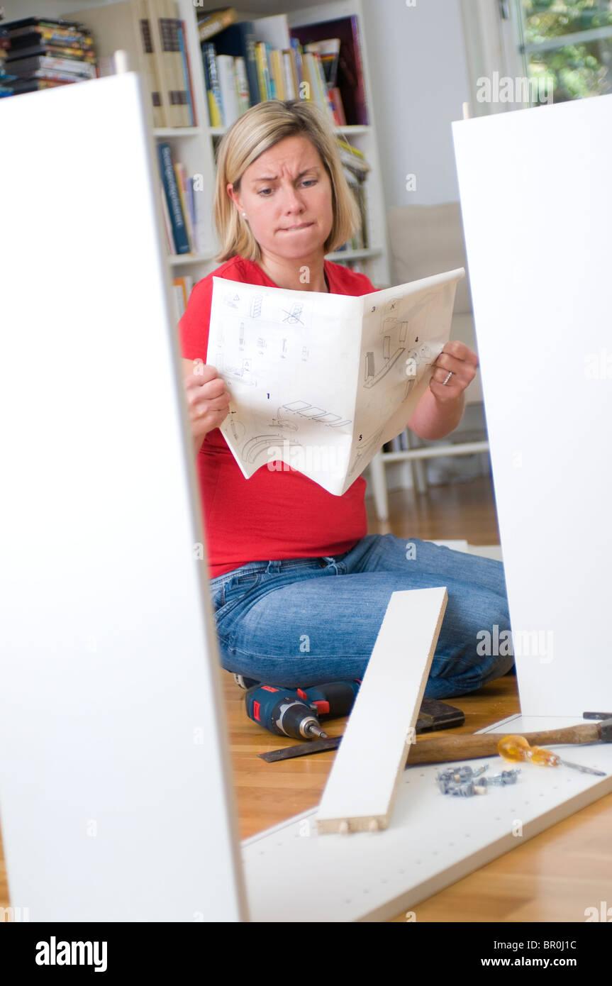 Giovane donna confusa da flat-imballato istruzioni di mobili Immagini Stock