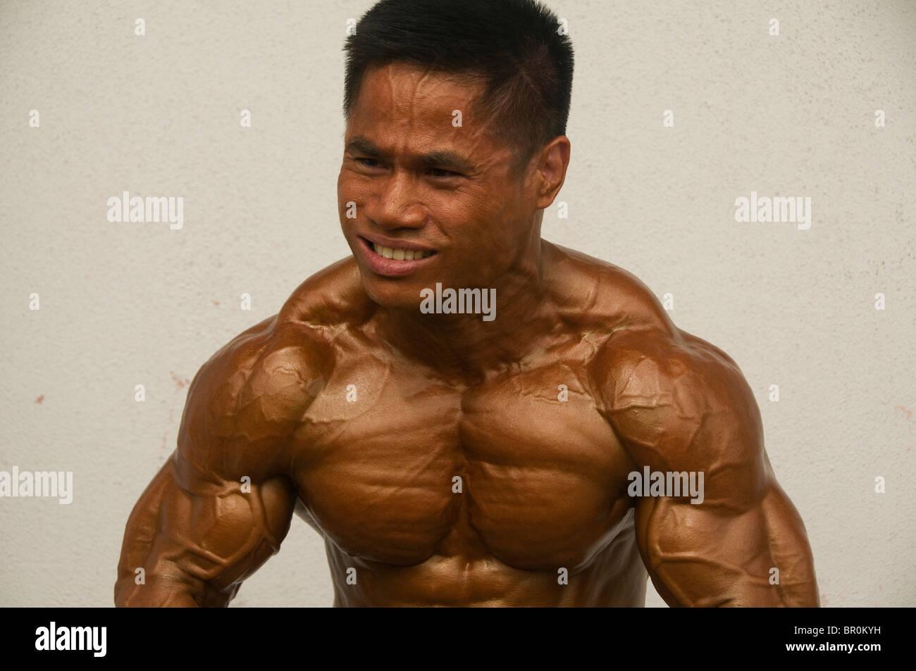 Allestitore mostra i suoi muscoli in un concorso a Bangkok in Tailandia Foto Stock