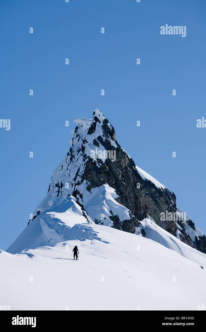 Telemark lo sciatore percorre backcountry sulla soleggiata cielo blu di giorno. Immagini Stock
