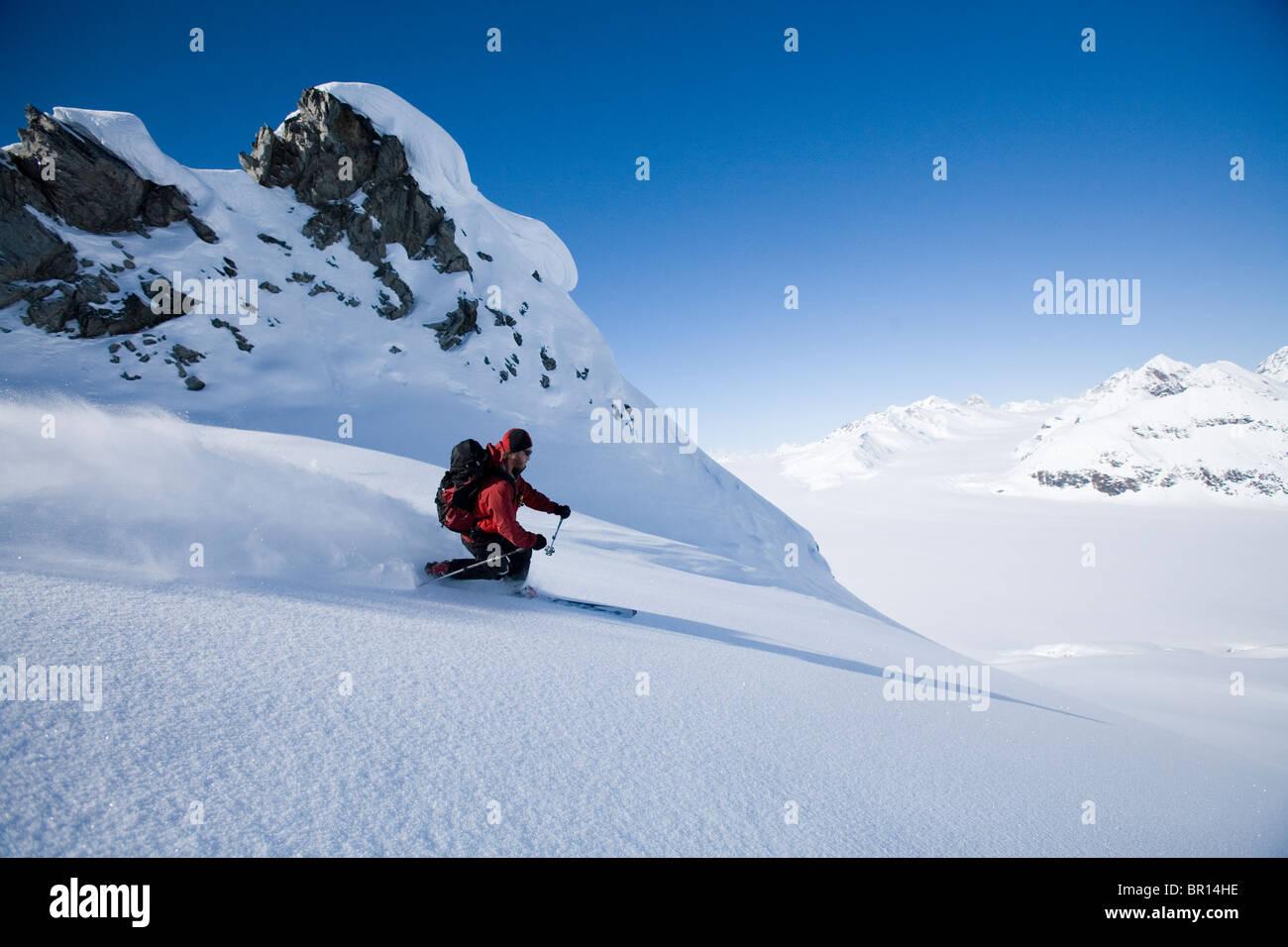 Uomo di telemark sci giù per la collina in Alaska backcountry vicino i confini del Canada Immagini Stock