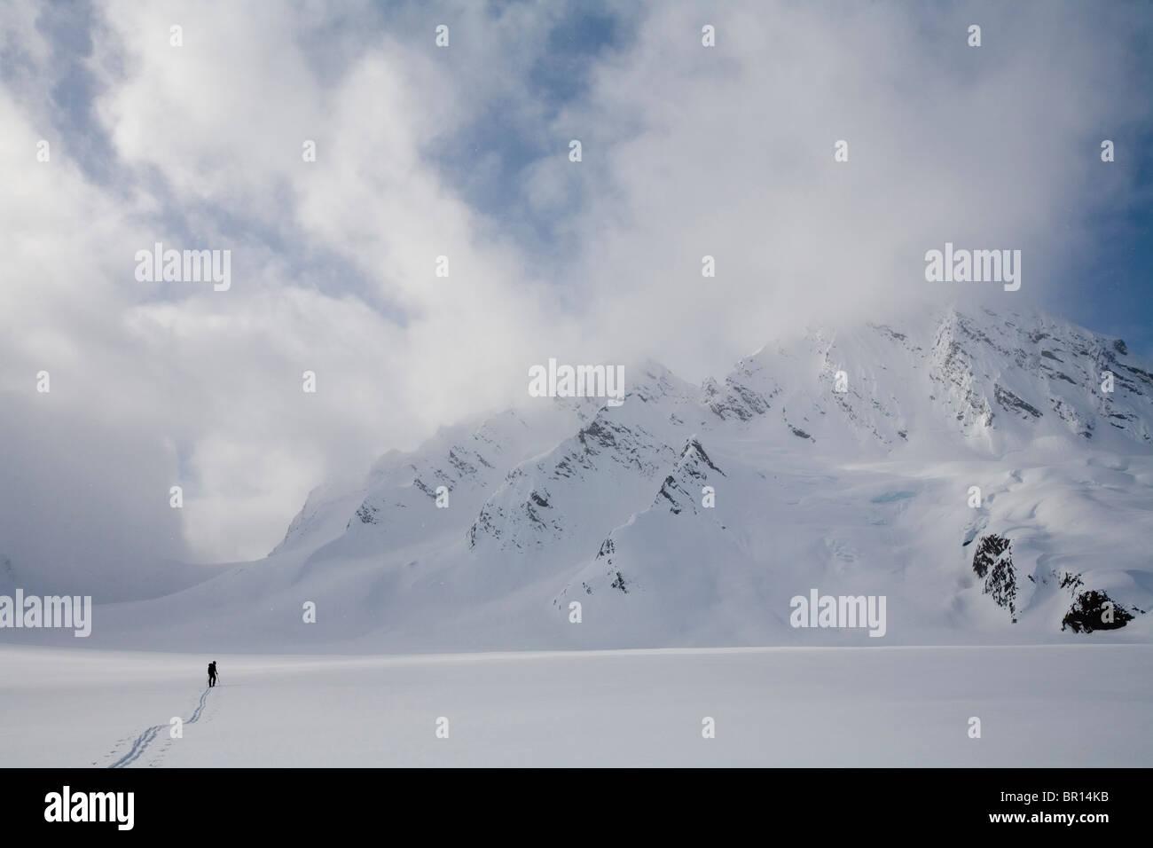 Backcountry rider attraversa il Glacier in tarda giornata cielo tempestoso. Foto Stock