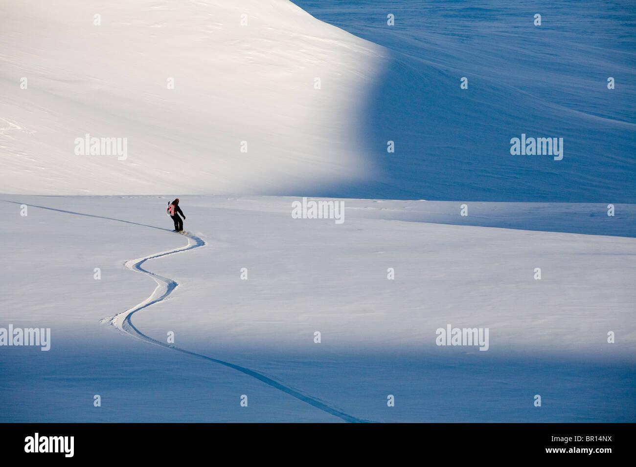 L'uomo Snowboard giù in leggera pendenza nel tardo pomeriggio. Immagini Stock