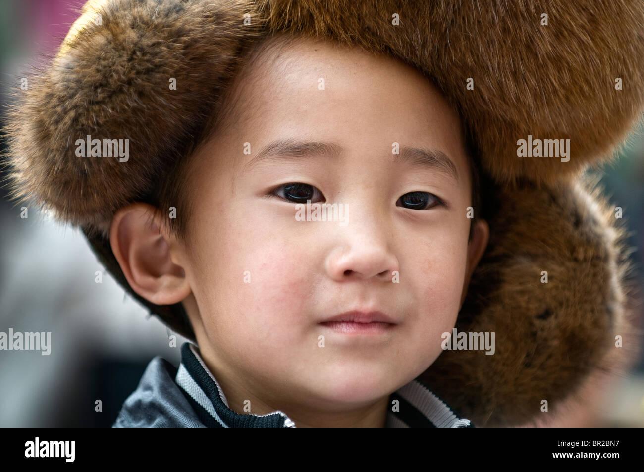 Tibetano etnica giovane ragazzo che indossa il cappuccio di pelliccia  frequentare il ballo folk e musica 73e69ea3d152