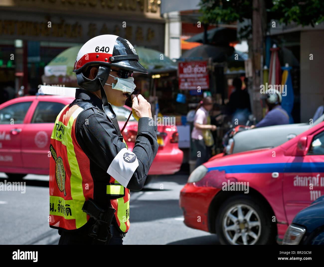 Polizia tailandese officer indossando un anti inquinamento maschera in Bangkok inquinamento elevato flusso di traffico. Immagini Stock