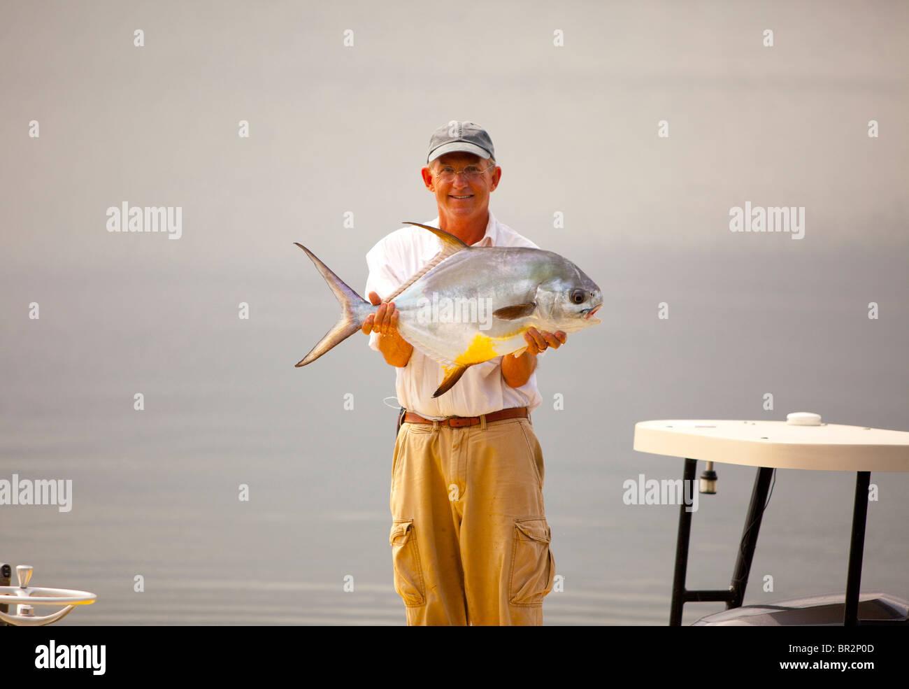 Ritratto di pescatore tenendo un pesce pescato Immagini Stock