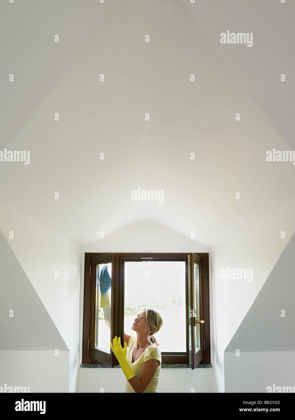 Metà donna adulta tergi windows in mansarda. Forma verticale, vita, spazio di copia Immagini Stock
