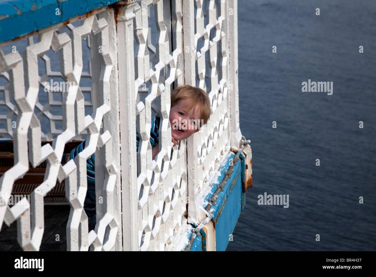 Cheeky giovane ragazzo cerca attraverso le ringhiere sul molo a Llandudno North Wales Immagini Stock
