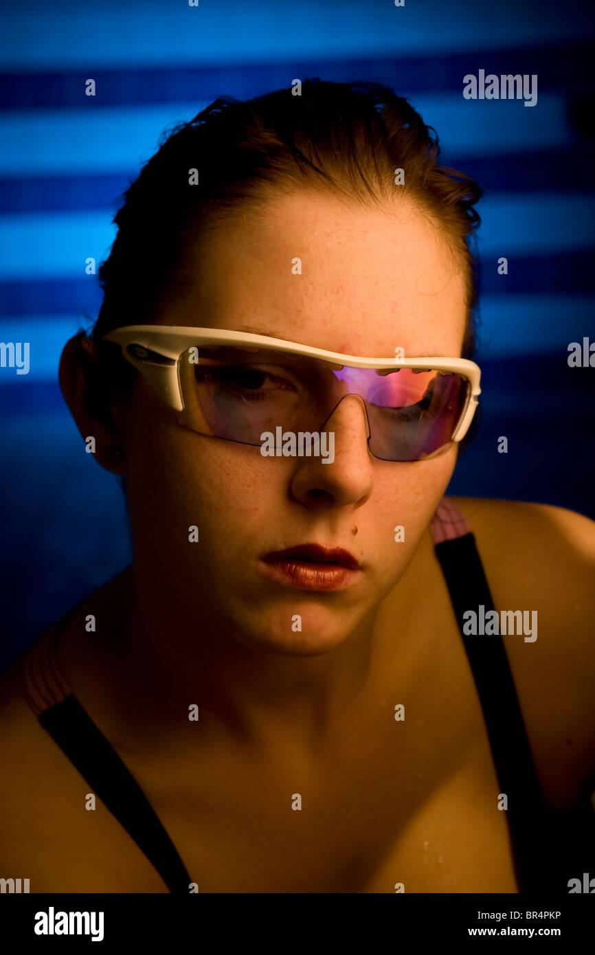 Ritratto di una donna bellissima con gli occhiali in piscina con uno sfondo blu Immagini Stock