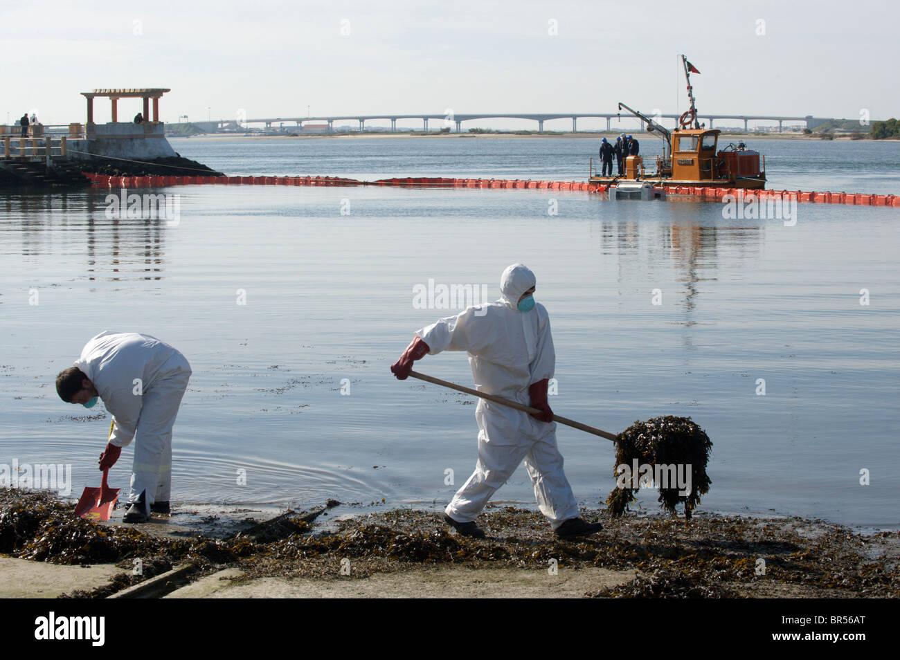 Gli uomini in pieno-corpo Indumenti di protezione e le maschere di respirazione pulire il dock mentre una barca Immagini Stock
