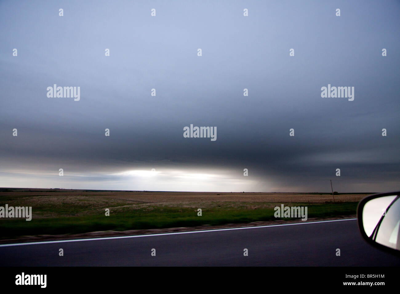 Foto guardando fuori dalla finestra di una vettura in movimento mentre si inseguono una tempesta. Immagini Stock