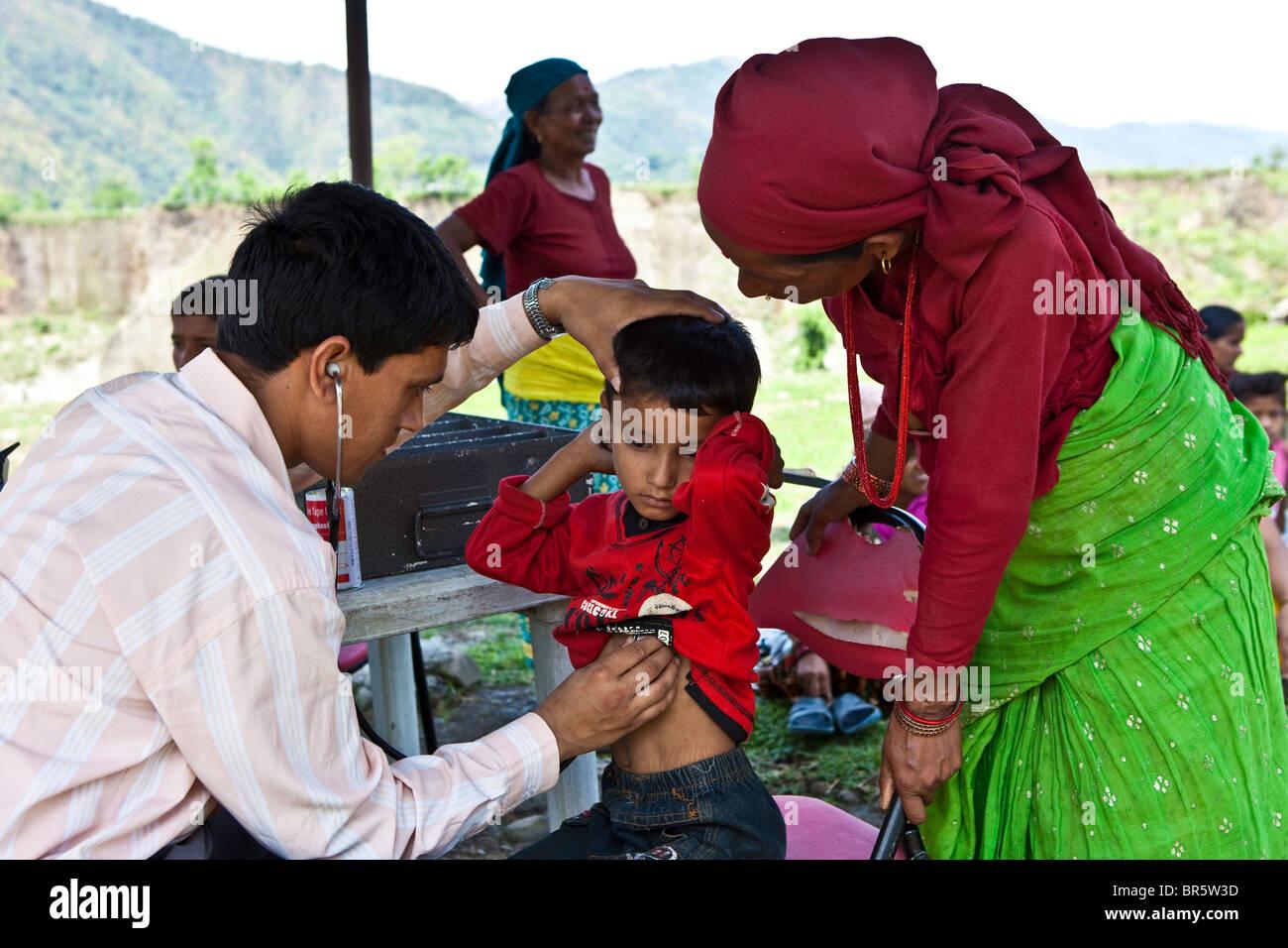 Medico controlla un bambino a Child Welfare Scheme Nepal (CWSN) mobile health clinic in Nepal. Immagini Stock