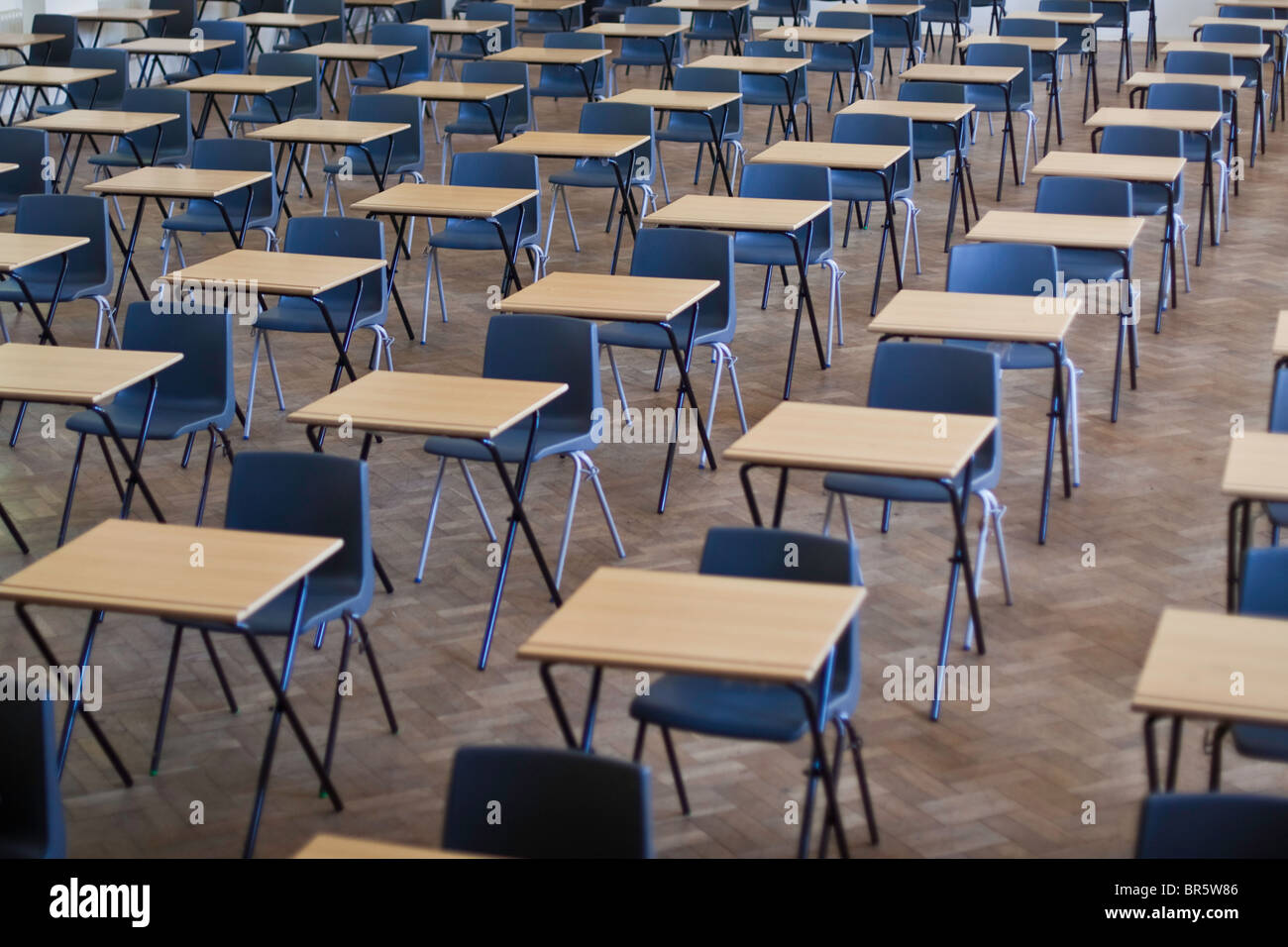 Scrivanie e sedie stabiliti per gli esami in una scuola hall nel Regno Unito. Foto Stock
