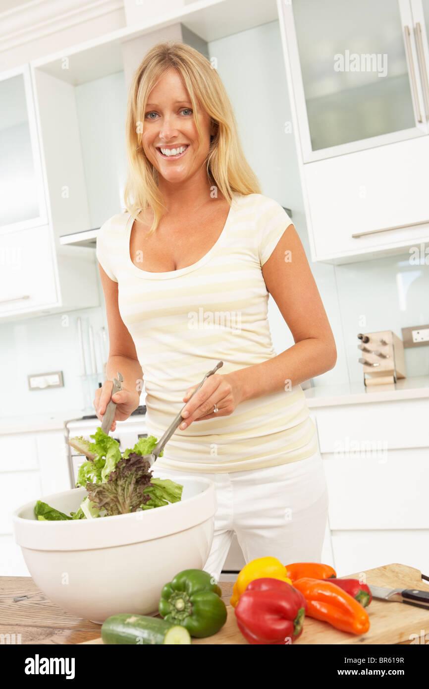 La donna la preparazione di insalata in cucina moderna Foto Stock