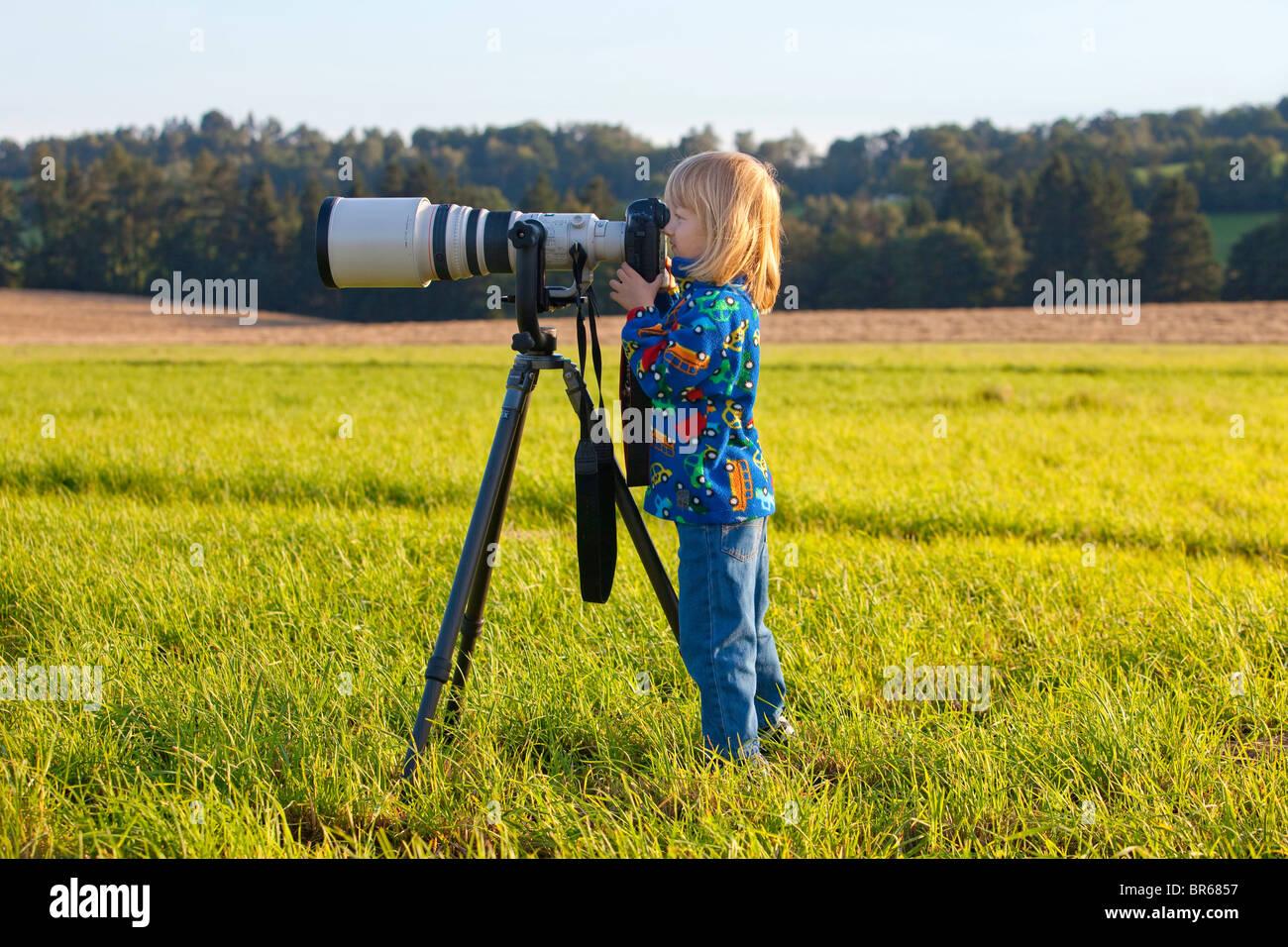 Ragazzo che guarda attraverso super teleobiettivo sulla fotocamera digitale Immagini Stock