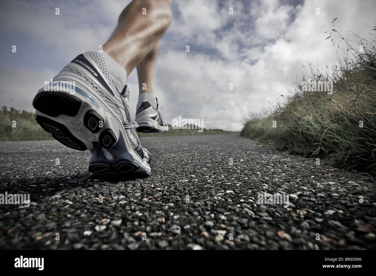Un vicino a basso angolo di visione di un maschio di atleta che corre lungo una strada asfaltata con i suoi grandi Immagini Stock